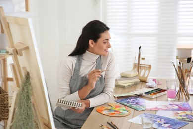 Young woman drawing on easel in studio