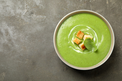 Tasty homemade zucchini cream soup on grey table, top view. Space for text