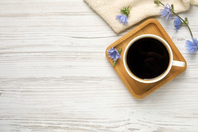Cup of delicious chicory drink and flowers on white wooden table, flat lay. Space for text