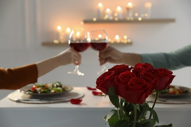 Couple having romantic dinner at home, focus on red roses