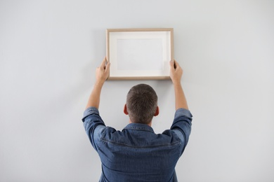 Man hanging picture on white wall indoors. Interior decoration