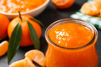 Tasty tangerine jam in glass jar on dark table, closeup. Space for text