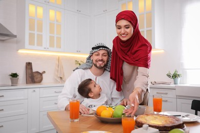 Happy Muslim family eating together in kitchen