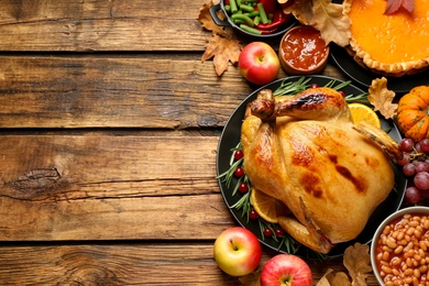Traditional Thanksgiving day feast with delicious cooked turkey and other seasonal dishes served on wooden table, flat lay. Space for text