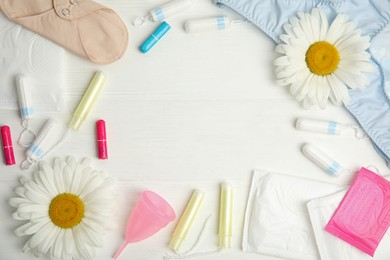 Frame of tampons and other menstrual hygienic products on white wooden background, flat lay. Space for text
