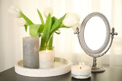 Burning candles, mirror and flowers on black table indoors