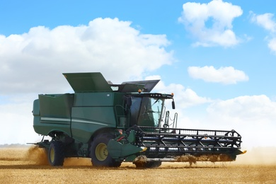 Modern combine harvester working in agricultural field