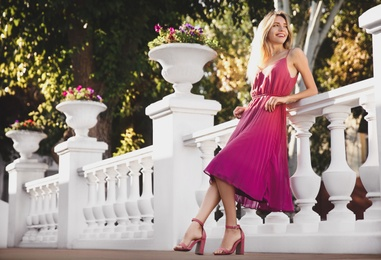 Beautiful young woman in stylish pink dress near vintage railing outdoors