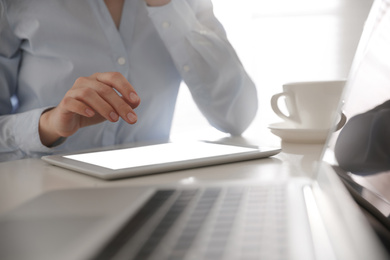 Businesswoman working with modern tablet at table in office, closeup