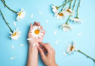 Woman with beautiful chamomile flowers on color background, top view