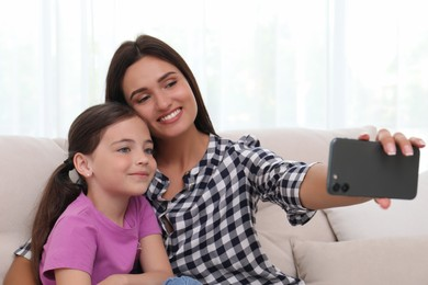 Happy mother and daughter taking selfie together at home. Single parenting
