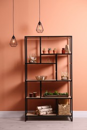 Shelving with different decor, houseplants and firewood near coral wall. Interior design
