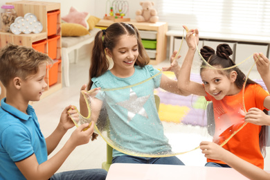 Happy children playing with slime at table indoors