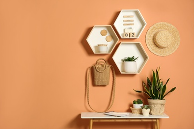 Shelves and table with decorative elements on color wall. Space for text