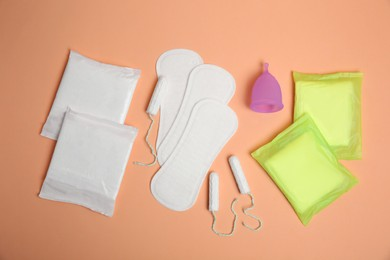 Menstrual pads and other period products on pale orange background, flat lay