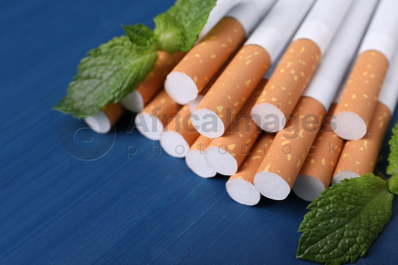 Menthol cigarettes and mint leaves on blue wooden table, closeup. Space for text