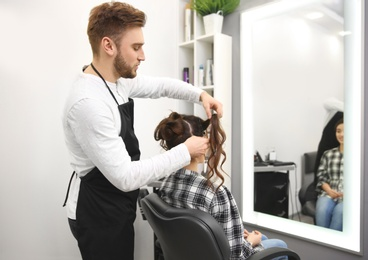 Professional male hairdresser working with client in salon