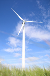 Wind turbine in field on sunny day, low angle view. Alternative energy source
