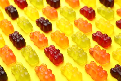 Delicious gummy bear candies on yellow background, closeup