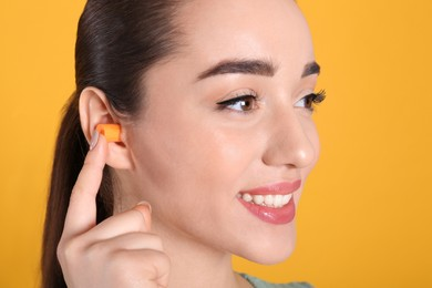 Young woman inserting foam ear plug on yellow background, closeup