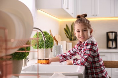 Little girl washing dishes in kitchen at home