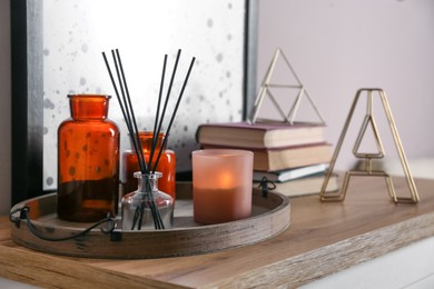 Wooden tray with air reed freshener and candles on table indoors
