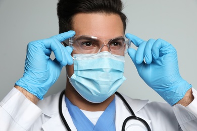 Doctor in protective mask, glasses and medical gloves against light grey background