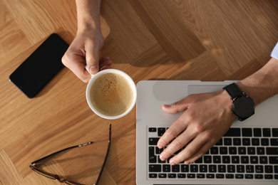 Man with laptop, cup of coffee and smartphone at wooden table, top view