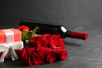 Beautiful red roses, gift box and bottle of wine on grey table, space for text. Valentine's Day celebration