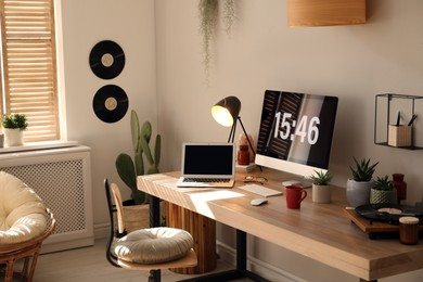 Room interior with comfortable workplace. Modern computer and laptop on wooden desk