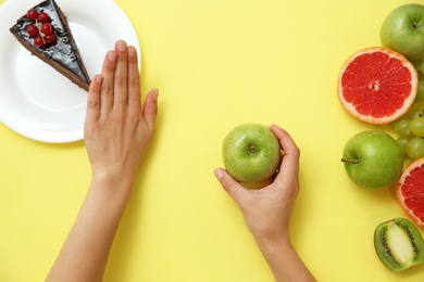 Top view of woman choosing between cake and healthy fruits on yellow background, closeup