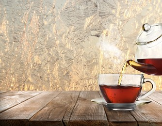 Pouring tea into glass cup on wooden table near window covered with frost