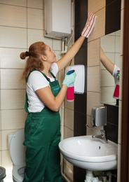 Professional janitor cleaning wall with supplies in restroom