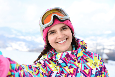 Young woman taking selfie at mountain resort. Winter vacation