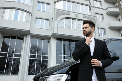 Handsome young man near modern car outdoors, low angle view