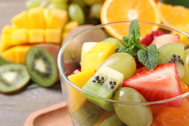 Delicious fresh fruit salad in dish on table, closeup view