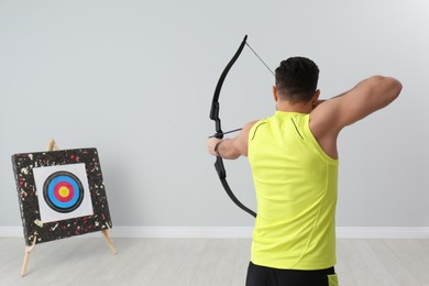 Man with bow and arrow aiming at archery target indoors