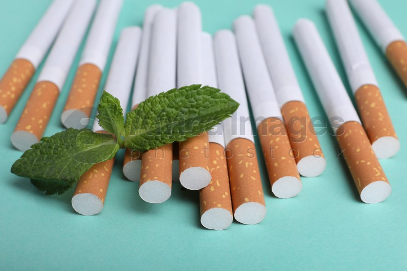 Menthol cigarettes and mint on turquoise background, closeup