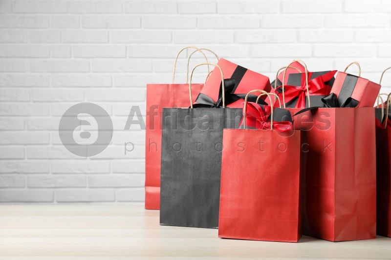 Paper shopping bags and gift boxes on table near white brick wall, space for text. Black Friday sale