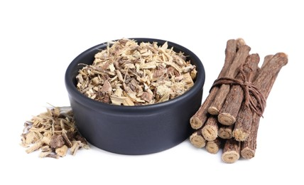 Dried sticks of liquorice root and shavings on white background