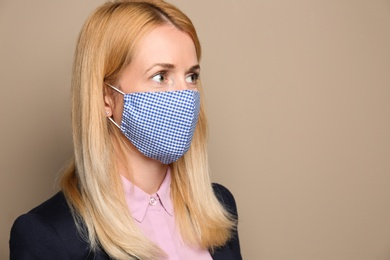 Woman wearing handmade cloth mask on beige background, space for text. Personal protective equipment during COVID-19 pandemic