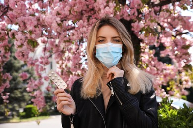 Woman with pills and protective mask near blossoming tree outdoors. Seasonal pollen allergy