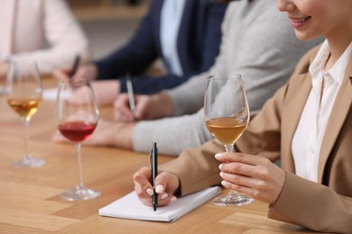 Sommeliers tasting different sorts of wine at table indoors, closeup