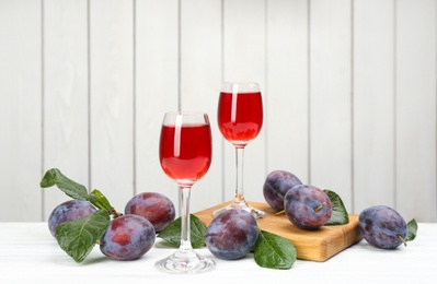 Delicious plum liquor and ripe fruits on table against white background. Homemade strong alcoholic beverage