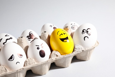 Yellow smiley egg among others with negative emotions in package on light background