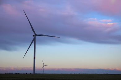 Beautiful view of field with wind turbines in evening. Alternative energy source