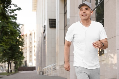 Handsome mature man running on street, space for text. Healthy lifestyle