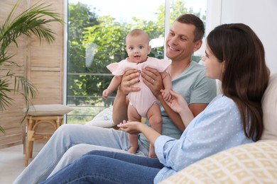 Happy family with their cute baby in living room at home