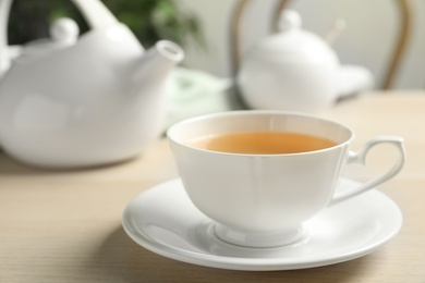 Cup of hot green tea on wooden table indoors