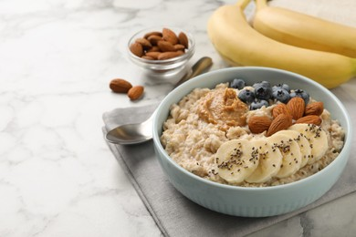 Tasty oatmeal porridge with toppings on white marble table, space for text